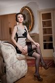 Happy smiling attractive woman wearing an elegant dress and black stockings sitting on the sofa arm.