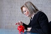 Businesswoman Put Coins Into Piggy Bank