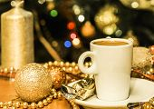Cup Of Coffee And Gold Christmas Decorations At Christmas Tree