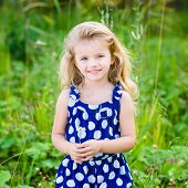 Beautiful Smiling Little Girl With Long Blond Curly Hair And Flower In Her Hands