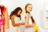 African girl helps another one to fit white dress