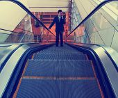 a businessman riding an escalator toned with a retro vintage instagram filter effect