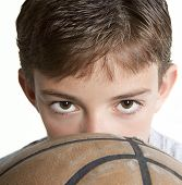 picture of young boy  - Young teen peering over the top of a basketball - JPG