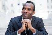 foto of staircases  - Cheerful young African man in formalwear keeping hands clasped and looking away while sitting at the outdoors staircase - JPG
