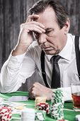 picture of poker hand  - Depressed senior man in shirt and suspenders holding head in hand while sitting at the poker table with money and gambling chips laying all around him - JPG