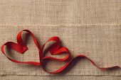 Two Hearts On Sackcloth Burlap Background. Valentine Day Or Wedding Love Concept. Ribbon Shape As Jo