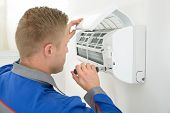 image of air conditioner  - Portrait Of Young Male Technician Repairing Air Conditioner - JPG