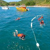 A Group Of Tourists Snorkeling On Blue Sea Water In The Beach, Larn Island, Pattaya, Thailand