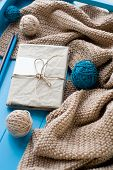 image of blanket snow  - One old notebook in knitted cover lie next to the coil bright filaments and blanket knitted on blue background - JPG
