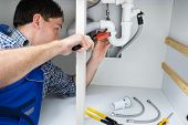 pic of plumber  - Portrait Of Male Plumber Fixing A Sink In Bathroom - JPG