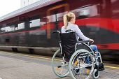 stock photo of wheelchair  - a young woman sitting in a wheelchair at a train station - JPG