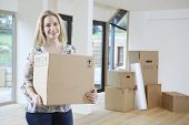 Woman Moving Into New Home With Packing Box