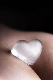 foto of sadism  - closeup of an female butt with icecube heart - JPG