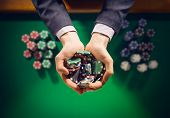 stock photo of poker hand  - Elegant male casino player holding a handful of chips with green table on background hands close up top view - JPG
