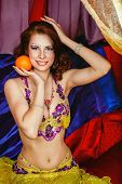 image of harem  - Young oriental beauty sitting in a tent and holding an orange - JPG