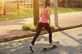 stock photo of skateboard  - one young asian woman skateboarder skateboarding outdoor - JPG