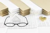 foto of piles  - Spectacles and house with pile of gold coins on finance account have pile of paperwork with envelope as background - JPG