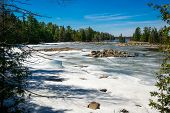 stock photo of inlet  - The spring thaw melts the snow covering a lake inlet in the wilderness of Ontario Canada - JPG