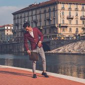 image of blazer  - Young handsome Asian model dressed in red blazer posing by an rtificial basin - JPG