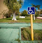 stock photo of handicap  - Blue handicapped sign with wheelchair at tropical street - JPG
