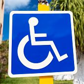 pic of handicap  - Blue handicapped sign with wheelchair at tropical street - JPG