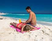 image of sun tan lotion  - Man applying sun lotion on a woman back summer tropical beach vacation - JPG