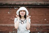 picture of blouse  - Young woman in a white blouse and hat posing on a blurred background old vintage brown brick wall - JPG