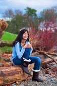 stock photo of biracial  - Young biracial teen girl in blue shirt and jeans sitting on large log on rocky beach by lake - JPG