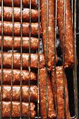 stock photo of charcoal  - grilled roast beef lamb sausages on bbq grid over charcoal - JPG