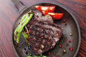 pic of peppercorns  - fresh roast beef fillet mignon on old retro style cast iron pan on retro wooden table as background with rosemary peppercorn and tomatoes - JPG