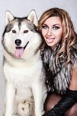 stock photo of mimicry  - Beautiful young woman with a husky dog over grey background - JPG