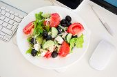 image of greek food  - Greek salad in the workplace near the mouse and keyboard with monitor - JPG