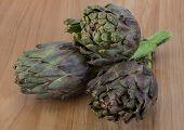 picture of artichoke hearts  - Fresh Raw artichokes on the wooden background - JPG