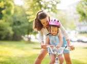 stock photo of encouraging  - An encouraging mother helps her daughter learn how to steer her new bicycle - JPG