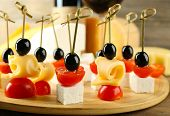 foto of canapes  - Cheese canapes with cherry tomatoes and olives on table close up - JPG