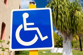 image of handicapped  - Blue handicapped sign with wheelchair at tropical street - JPG
