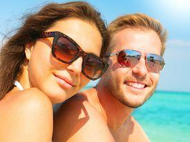 image of hot couple  - Happy Couple in Sunglasses having fun on the Beach - JPG