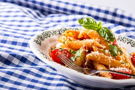 pic of pene  - Plate with pasta pene Bolognese sauce cherry tomatoes parsley top and basil leaves on checkered blue tablecloth - JPG