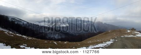 Picture or Photo of Panoramic picture of mountains with clouds floating near the mountain top