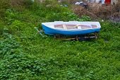 Постер, плакат: old boat abandoned on the field