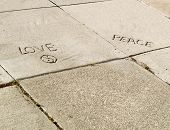 stock photo of heartfelt  - heartfelt carved sidewalk graffiti encourages love and peace - JPG