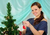 picture of tawdry  - Young pregnant girl dresses up Christmas tree - JPG