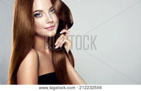 poster of Young, brown haired woman  with voluminous hair.Beautiful model with long, dense, straight hairstyle and vivid makeup, is touching own hair with tenderness. Symbol of attentiveness to hair and good care of it. Perfect hair  and sexy look.Incredibly dense,