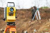 Teodolito de equipo Surveyor en trípode en construcion frente a Inspector de trabajo