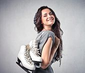 Smiling young woman carrying a pair of ice skates
