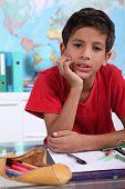 kleiner Junge auf seinem Schreibtisch Schule