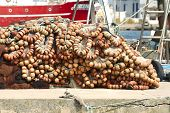 View Of A Pile Of Orange Floaters On The Docks.