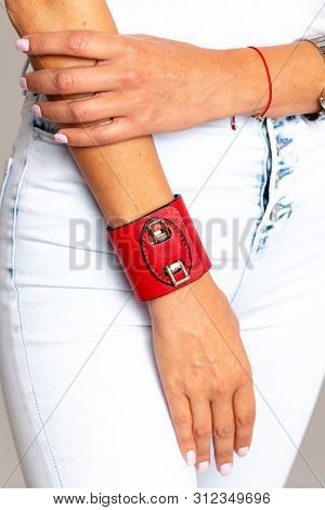 poster of Red Female Leather Bracelet With Iron Inserts On A Light Background.
