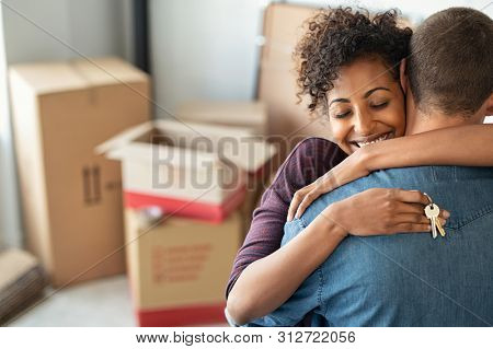 poster of Young african woman holding home keys while hugging boyfriend in their new apartment after buying re