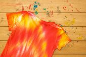 T-shirt In The Style Of Tie Dye Inverted On A Wooden Table. Staining Fabric In Tie Dye Style. Flat L poster